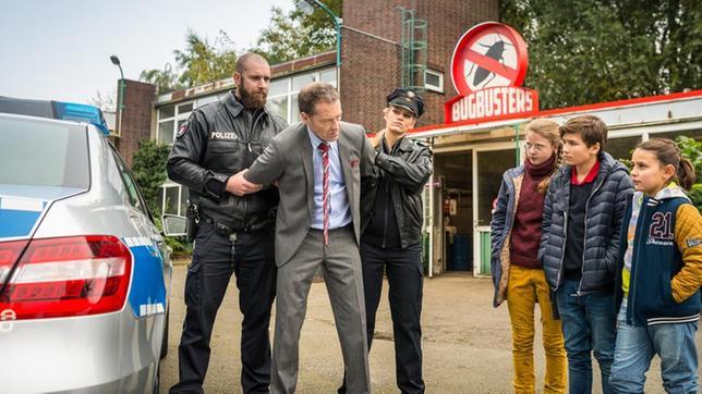 Geschäftsmann Lackmann (Oliver Sauer) wird von zwei Polizisten festgenommen. Pinja (Sina Michel), Ramin (Jann Piet) und Jale (Ava Sophie Richter) stehen daneben.