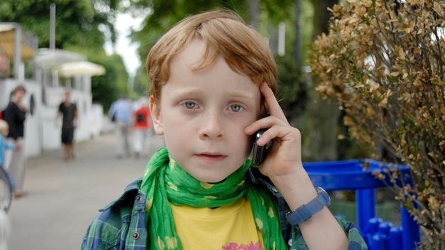 Henri hält ein Handy an sein Ohr