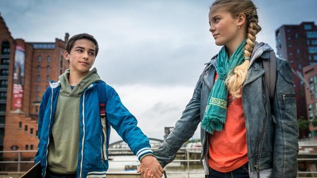 Jacob (Levin du Hamél) und Stella (Zoe Malia Moon) halten sich an der Hand.