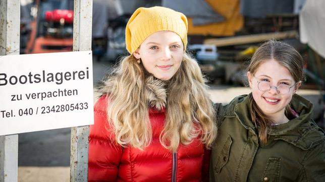 Stella (Zoë Malia Moon) und Pinja (Sina Michel) stehen neben einem Schild der Bootslagerei.