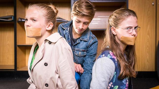 Till (Otto von Grevenmoor) kniet zwischen Stella (Zoe Malia Moon, links) und Pinja (Sina Michel), die ein Klebeband über den Mündern haben.