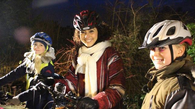 Kinder und Siham mit Fahrrad und Helm, lächelnd