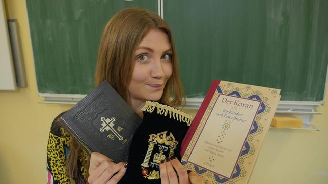 Reporterin Jana mit einer Bibel, einer Tora und einer deutschen Übersetzung des Koran