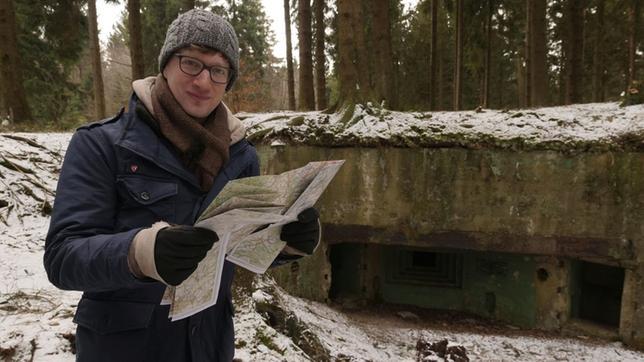 Robert steht mit Landkarte im Schnee vor einem Bunker im Wald