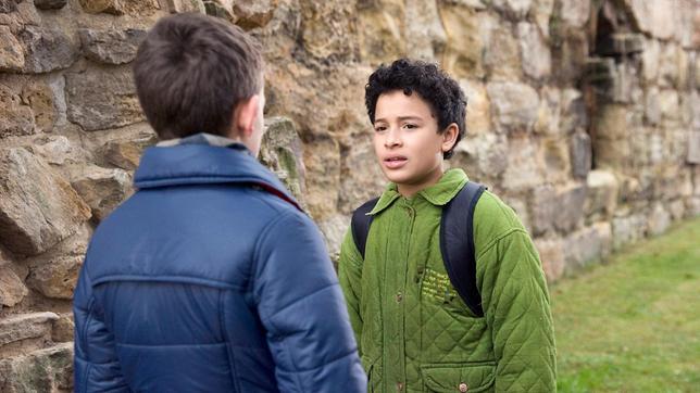 Raphael (Oskar-Kraska Mc Kone, re.) beichtet seinem Freund Dominik (Yannick Rau, li.), dass er in Daphne (Johna Fontaine) verliebt ist.