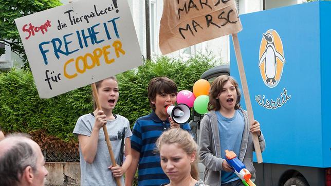 Leo(nie) (Phillis Lara Lau), Linus (Mathieu Harre) und Jan (Giuliano Marieni) demonstrieren vor der Eisdiele gegen dei Lebensbedingungen von Pinguin Cooper