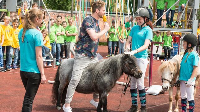 Moderator Johannes Zenglein auf einem Ponyneben drei Studiogästen