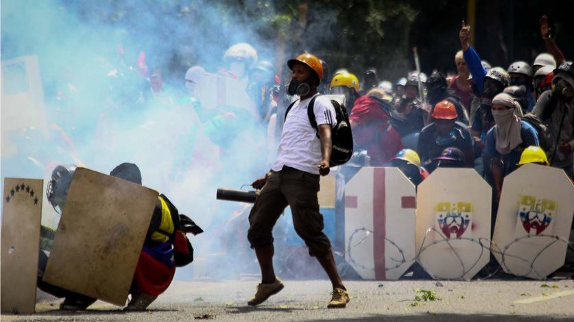 Demonstranten, vermummt und mit Schutzschilden