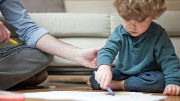 Ein kleiner Junge sitzt neben seinem Vater auf dem Boden und malt.