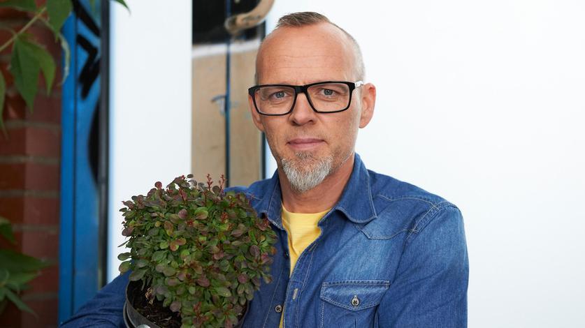 Thomas D mit einer Topfpflanze