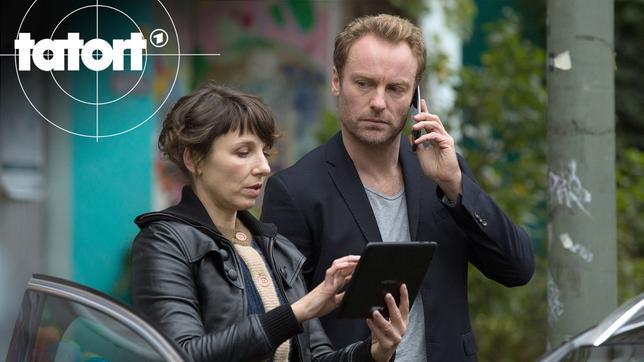Nina Rubin (Meret Becker) und Robert Karow (Mark Waschke) gleichen ein Foto mit einer Nachricht ab.