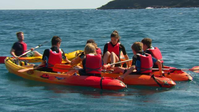 Coach Tobi überrascht die Gruppe am Strand mit Kanus.