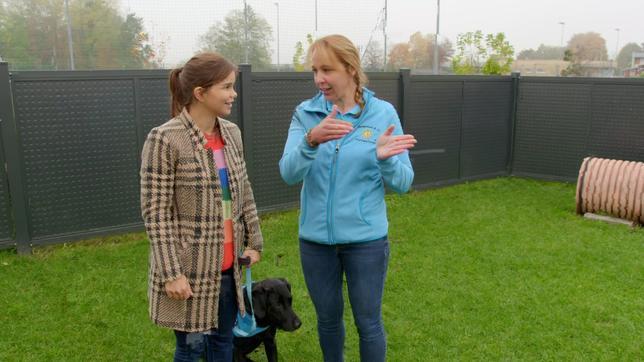 Anna mit einer Trainerin und einem Hund