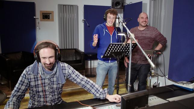 Julian (Mitte) und der Synchronsprecher und Dialekt-Imitator Oliver Lehmann (rechts) synchronisieren in einem Münchner Tonstudio.