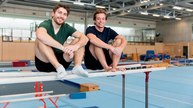 Tobi (rechts) checkt mit Turn-Trainer Erik, was er an den Geräten so drauf hat. Zum Beispiel am Barren, auf dem die beiden gerade sitzen.