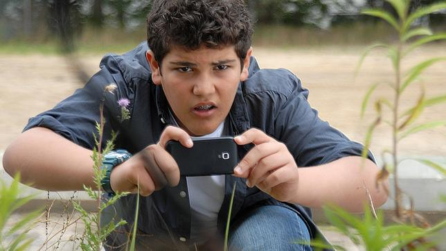Anton (Danilo Kamber) hält ein Smartphone in der Hand.