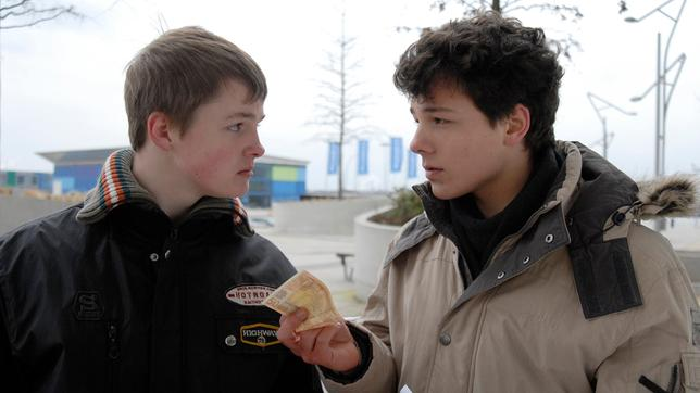 Ein Jugendlicher (Lukas Kieback, rechts) hält einem anderen (Maximilian Werner) einen Geldschein hin. Sie sehen sich an.
