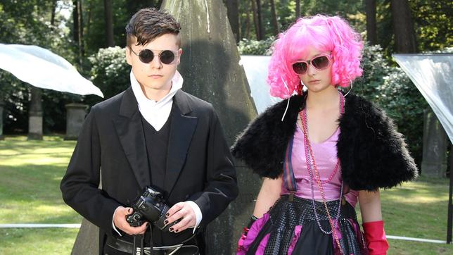 Ein Junge (Tom Böttcher) und ein Mädchen (Johanna Werner) mit Sonnenbrillen und auffälliger Kleidung stehen unter Bäumen.