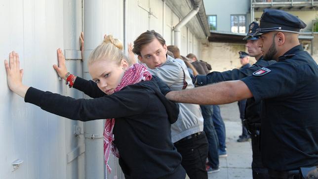 Eine junge Frau (Eva Nürnberg) und ein junger Mann (Alexander Finkenwirth) stehen mit anderen jungen Menschen mit den Händen an einer Wand. Hinter ihnen stehen Polizisten.