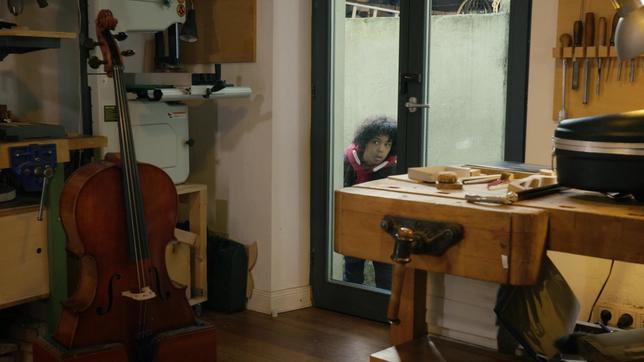 Femi schaut durch die Hintertür in den Laden des Geigenbauers.