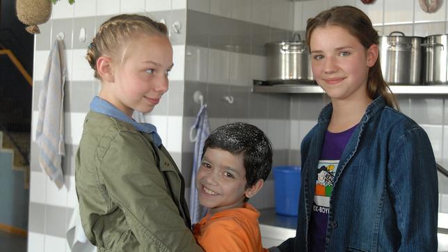 Jessi, Luis und Nina (Martha Fries, Emilio Sanmarino und Carolin Garnier) stehen lächelnd in einer Küche.