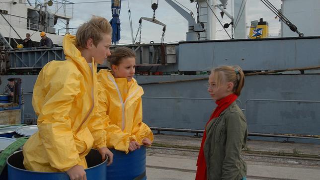 Jessi (Martha Fries, rechts) steht vor Max (Bruno Alexander) und Nina (Carolin Garnier), die mit Schutzanzügen in einer Tonne stehen, am Kai.