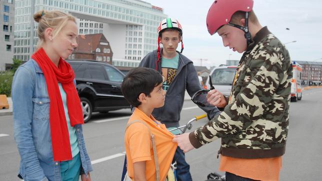 Jessi (Martha Fries) schaut zu einem Jungen mit BMX-Helm (David Riske), der eine Sonnenbrille in der Hand hält und Luis (Emilio Sanmarino, Mitte) am T-Shirt packt. Ein weiter Junge mit Helm schaut zu (Benjamin Falk, hinten)