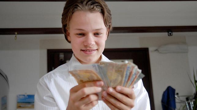 Leon (Luka Krause) hält lächelnd Geldscheine in der Hand.