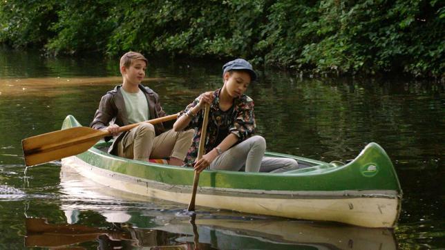 Lisha und Johannes sitzen in einem Boot auf dem Wasser.