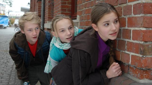 Max (Bruno Alexander), Jessi (Martha Fries) und Nina (Carolin Garnier) halten sich gedeckt an einer Hauswand.