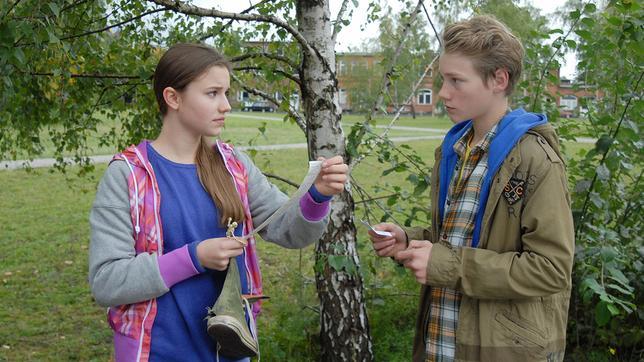 Nina (Carolin Garnier) hält einen alten Schuh und einen Papierstreifen in der Hand und schaut zu Max (Bruno Alexander), der neben ihr vor einer Birke steht.