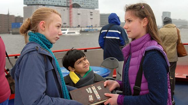 Nina (Carolin Garnier, rechts) übergibt Jessi (Martha Fries, links) und Luis (Emilio Sanmarino, Mitte) das Pfefferkörnerbuch.