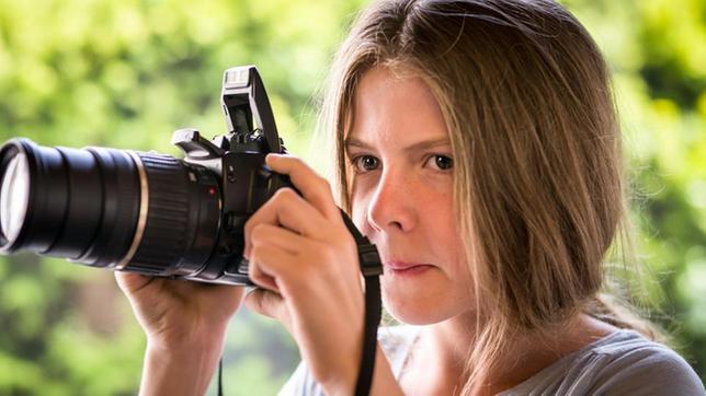 Pinja (Sina Michel) hält eine Kamera.