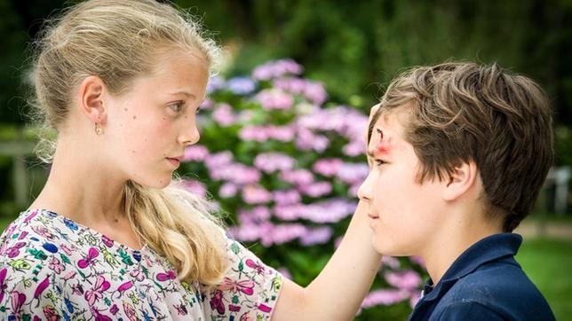 Stella (Zoë Malia Moon, li.) betrachtet eine Wund an Ramins (Jann Piet, re.) Stirn.