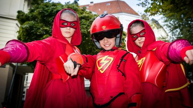 Stella (Zoë Malia Moon, links), der Rote Blitz (Lilly Barshy, Mitte) und Pinja (Sina Michel) in roten Superhelden-Kostümen.