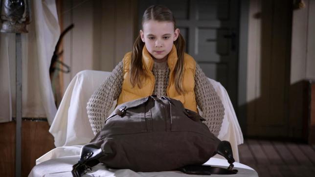 Szene aus Die Pfefferkörner Folge 186: Ein kleines Mädchen schaut sich einen großen Rucksack an.