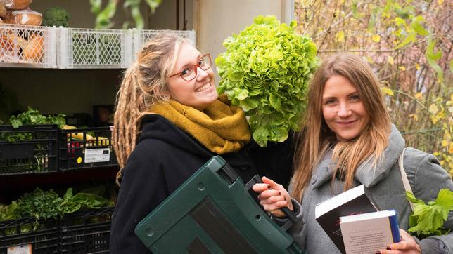 Jana steht zusammen mit Tine von foodsharing vor einem Stapel Kisten mit Lebensmitteln. Tine hält einen Salatkopf in der Hand, Jana eine Bohrmaschine und zwei Bücher.
