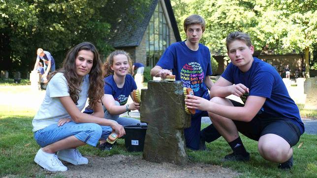 Mona hockt mit drei Jugendlichen um ein Steinkreuz. Sie halten Bürsten in der Hand und reinigen das Kreuz im Rahmen eines Workshops des Volksbunds.