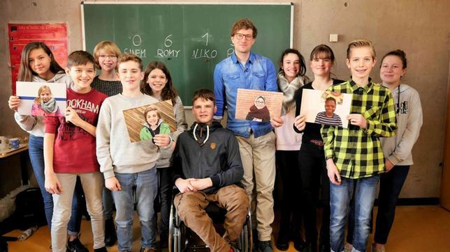 Robert mit einer Gruppe Schüler*innen vor einer Tafel. Sie halten einige großformatige Portraitfotos in den Händen.