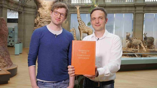 Robert neben dem Historiker Holger Löttel im Museum Koenig in Bonn. Holger Löttel hält ein Grundgesetz.