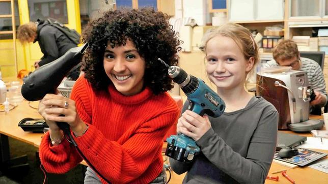 Siham mit einem Fön und ein Mädchen mit einer Bohrmaschine in einer Werkstatt
