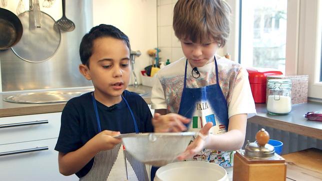 """Nino (li.) ist acht Jahre alt und hat richtig viele Hobbies: Er spielt Gitarre, liebt Fußball und schwimmt gerne. Ninos Papa kommt aus Frankreich und deshalb will Nino bei """"Schmecksplosion"""" für seine Freunde etwas typisch Französisches kochen: Es gibt Crê"""