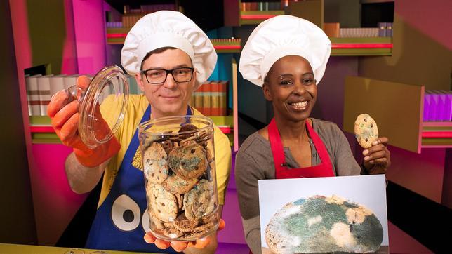"""Heute wird es eklig in der Ah!-Küche. Shary und Ralph backen Schimmelkekse- Iiiih! Aber keine Sorge! Es geht hier nicht um ein verdorbenes Lebensmittel, sondern nur um die perfekte Tarnung. Diese Kekse futtert nämlich bestimmt keiner weg! Während Shary und Ralph leckeren """"Fernsehschimmel"""" zaubern, klären sie gleichzeitig folgende Frage: Was sind Cookies und warum heißen sie so?"""