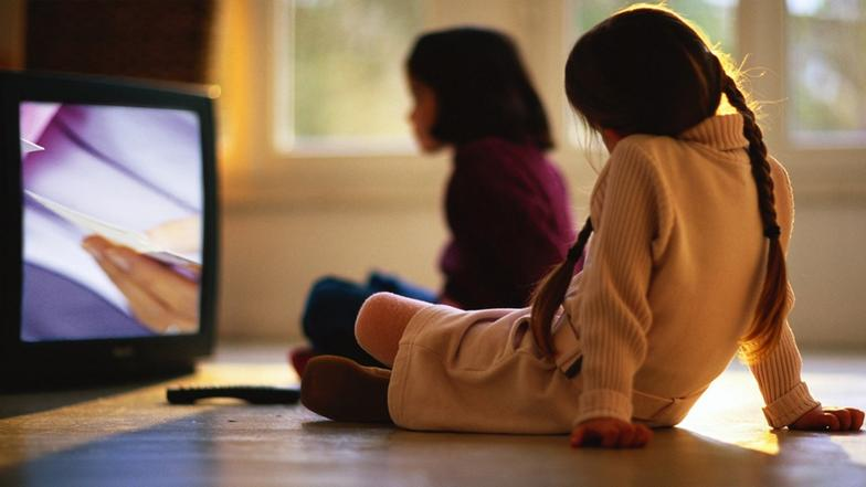 Zwei Mädchen sitzen am Boden vor einem Fernseher