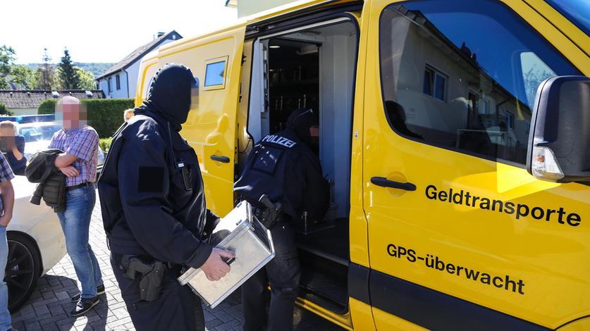 Schwerbewaffnete Polizisten beim Abtransport von Bargeld, das eine Clan-Familie in einem Wohnhaus gebunkert hatte.