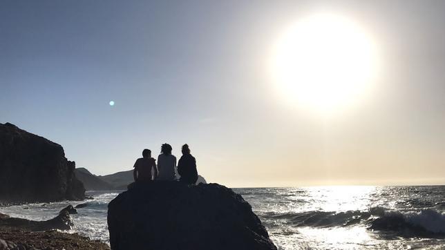 Die Jugendlichen genießen den Sonnenaufgang am Meer