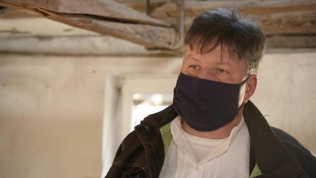 Ein Mann mit Mundschutz steht in einem Dachgeschoss.
