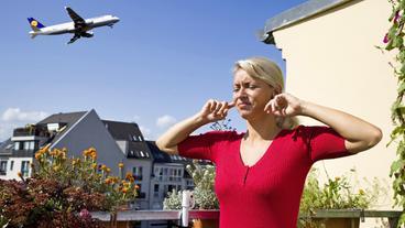 Eine Frau hält sich die Ohren zu, da hinter ihr ein Flugzeug startet.