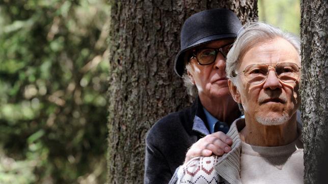 Fred Ballinger steht hinter Mick Boyle an einem Baum im Wald