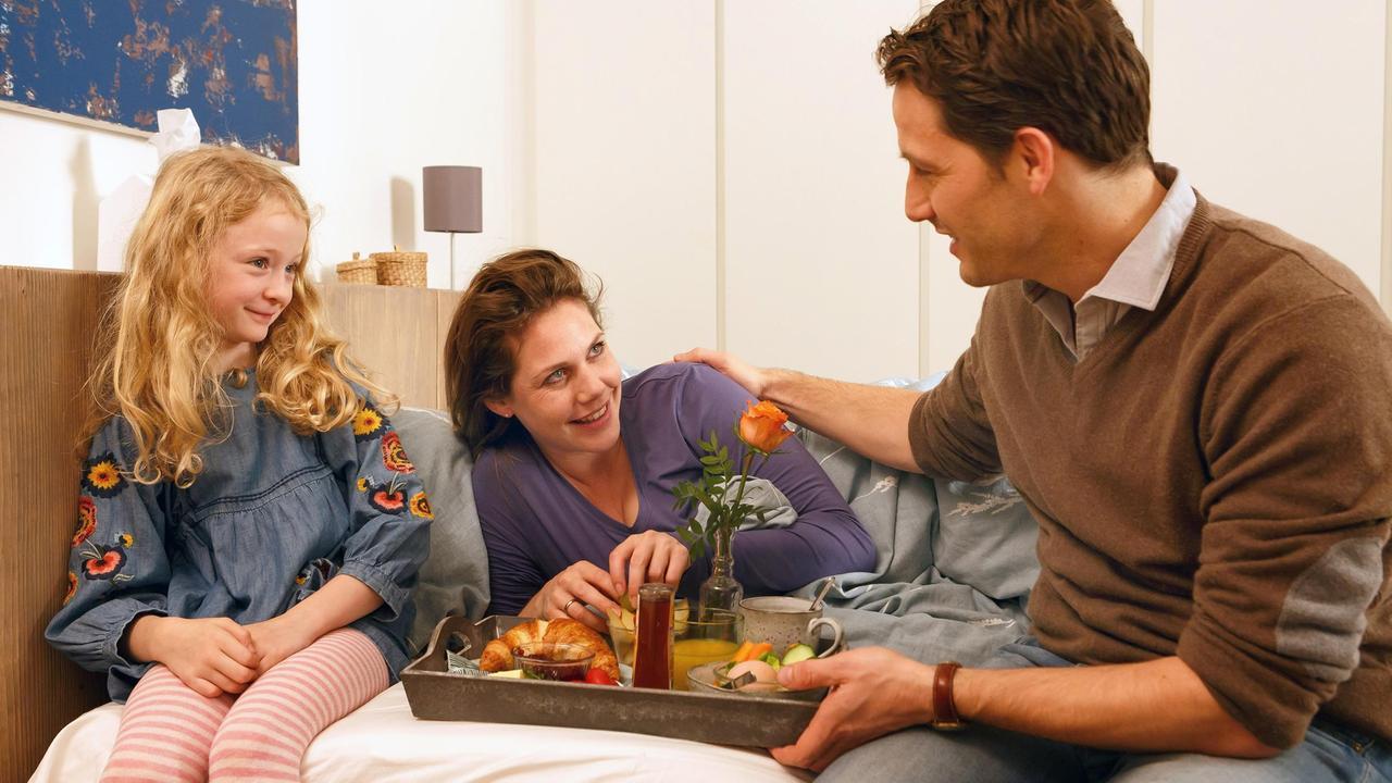 Anna, Judith und Mark im Schlafzimmer im Bett am Frühstücken